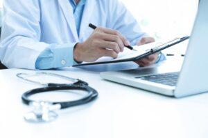 doctor-que-trabaja-computadora-portatil-que-escribe-papeleo-fondo-hospital_1421-69